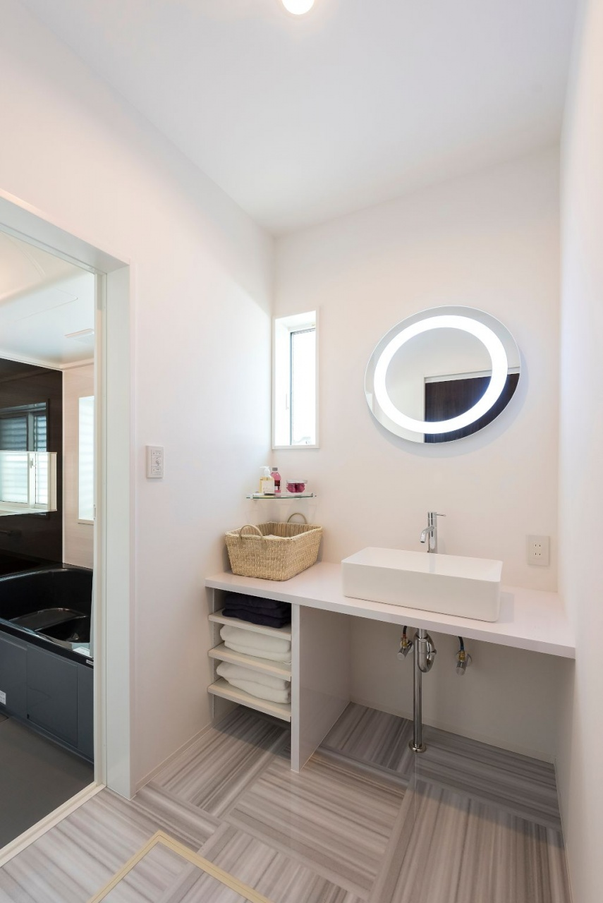 """洗面台の鏡は、照明が内蔵された""""女優ミラー""""。スクエアのシンクは丸い鏡と組み合わせた。"""