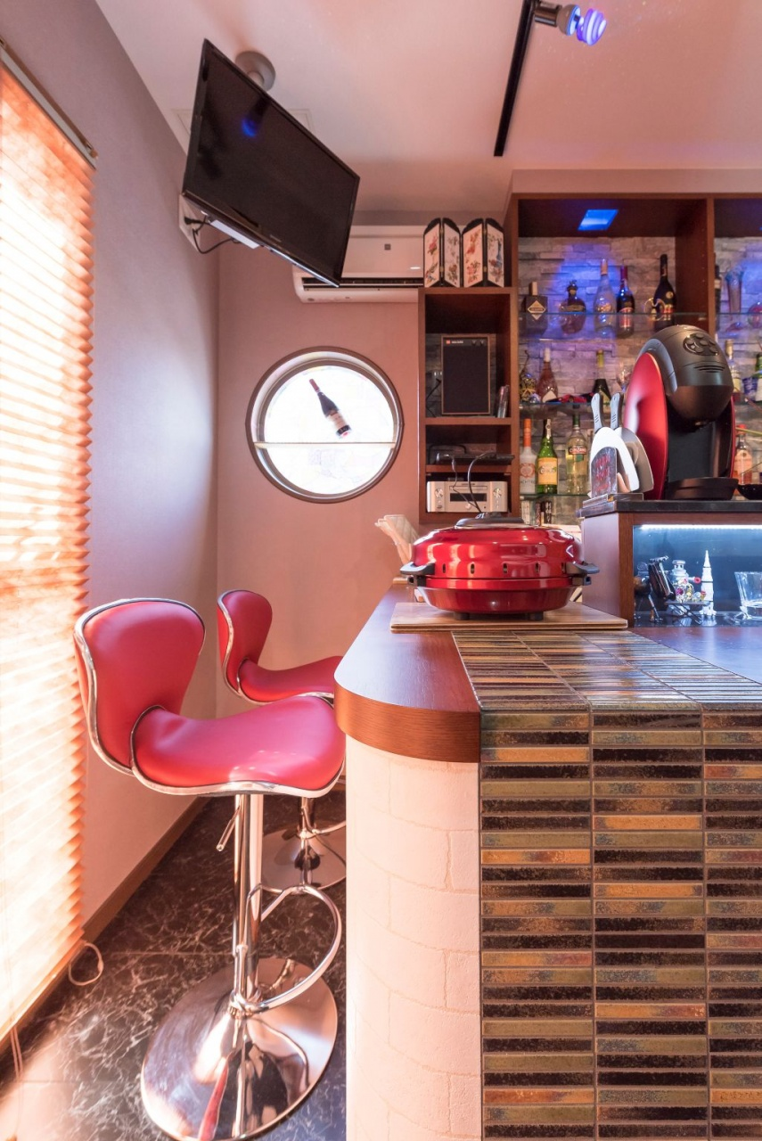 良いお酒が飲めそうなくつろぎのホームバー。AVモニター、カウンター、おしゃれな赤椅子がバーの雰囲気を演出。
