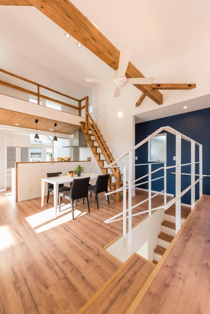 階段からは左右どちらにも回れる動線を確保。ダイニングとリビングはスキップフロアで空間にアクセントを。キッチン上部にはロフトもあり、縦空間の広がりも感じる