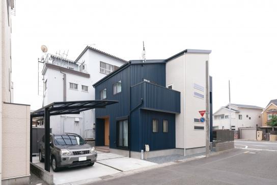 外壁はブルーのガルバリウムとサイディングのツートン。片流れの屋根と横スリット窓が外観のアクセント