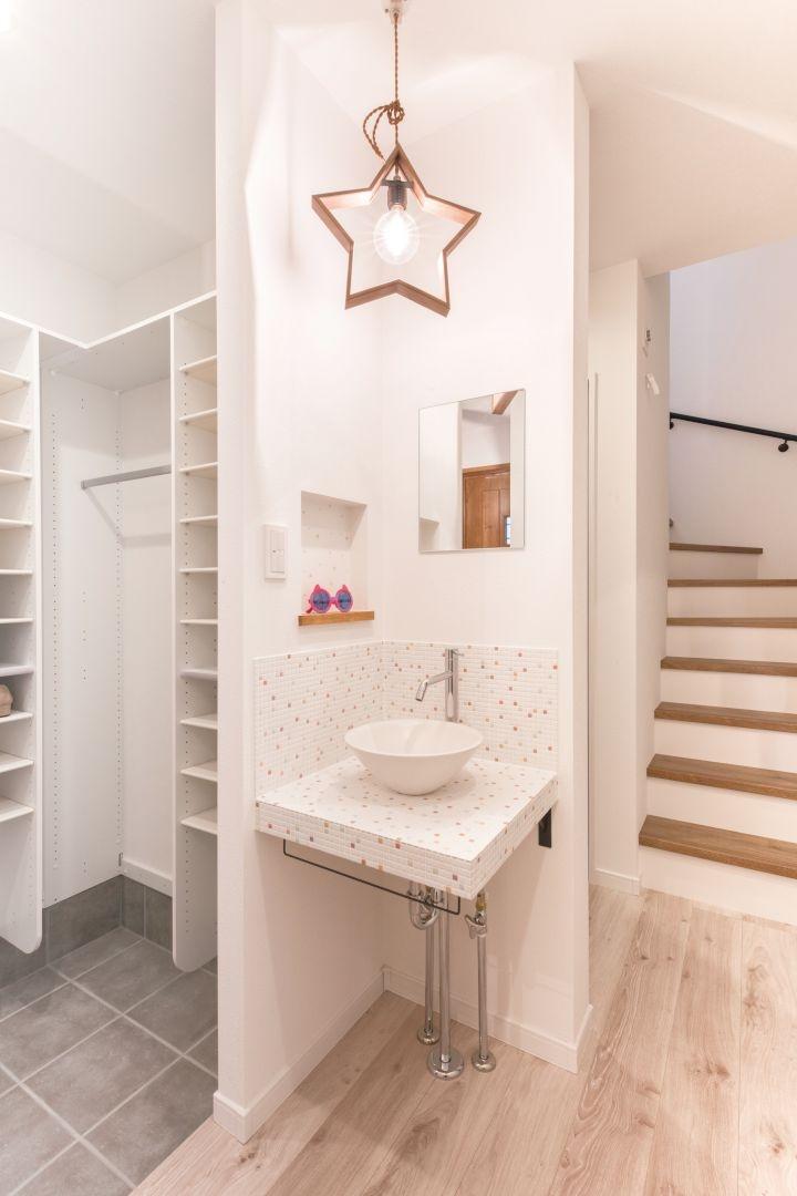 玄関ホールの手洗いは奥さまが選んだタイルとコーディネートした造作で