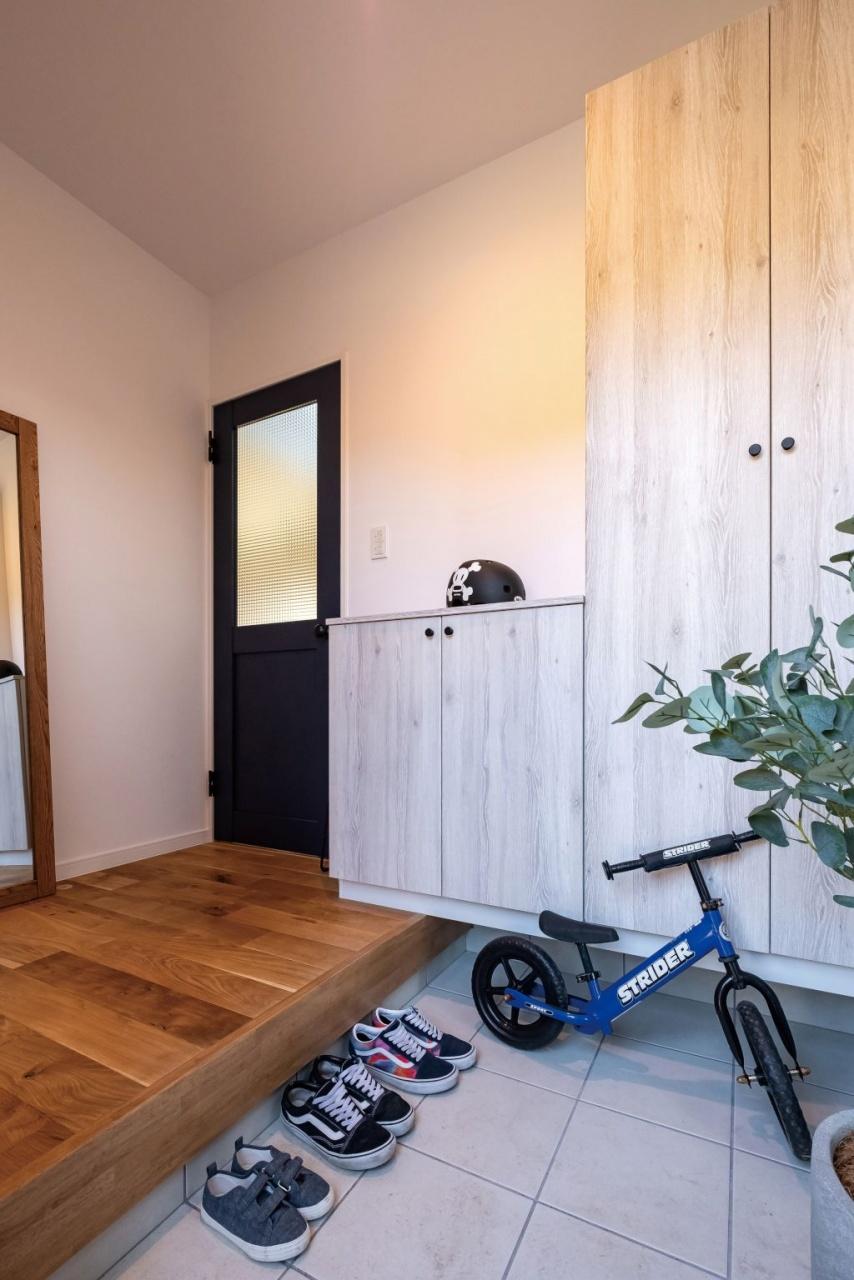 大きな靴箱は圧迫感がないように白っぽい木目調に。玄関ホールの床も無垢材にこだわって落ち着いた雰囲気に