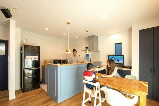 ブルーのカウンターを造作したキッチン。ゴールドのペンダントライトが華やぎを添える